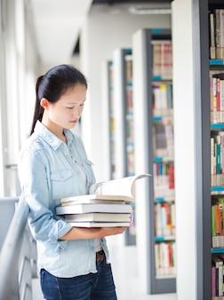 Étudiant tenant des livres dans la bibliothèque