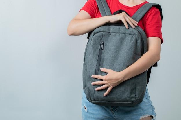 Étudiant tenant le sac à dos gris à l'avant