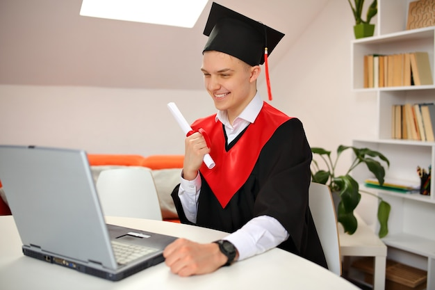 Un étudiant en toge et casquette d'angle est assis à la maison devant un ordinateur portable pendant la diffusion de la cérémonie de remise des diplômes