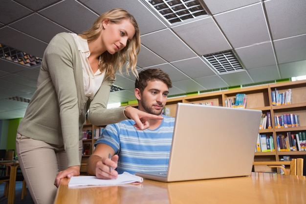 Etudiant en train de se faire aider par un tuteur en bibliothèque