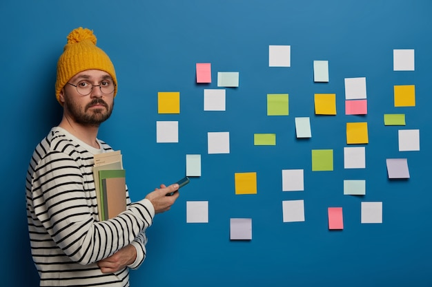 Un étudiant triste étudie pour l'examen, porte un chapeau jaune d'hiver et un pull décontracté, pose avec un téléphone portable et des manuels