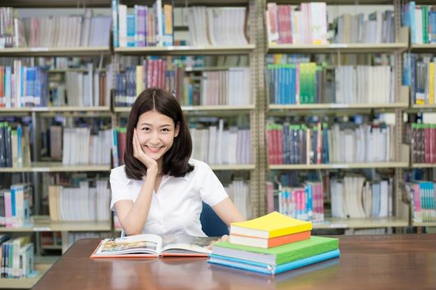 Étudiant en uniforme livre de lecture pour apprendre en bibliothèque à l'université.
