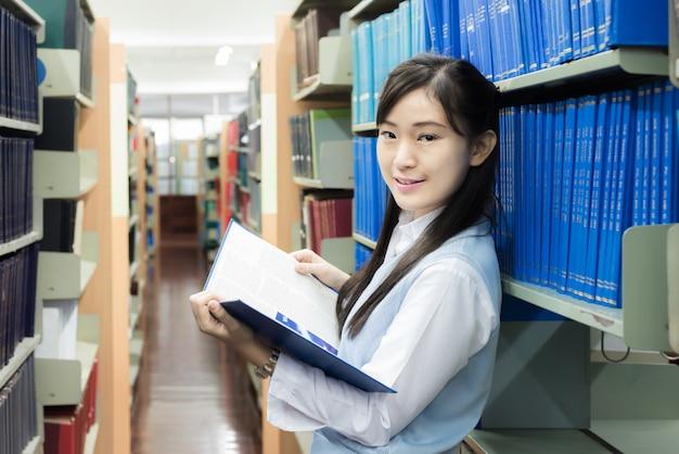 Étudiant en uniforme en train de lire à la bibliothèque de l'université.