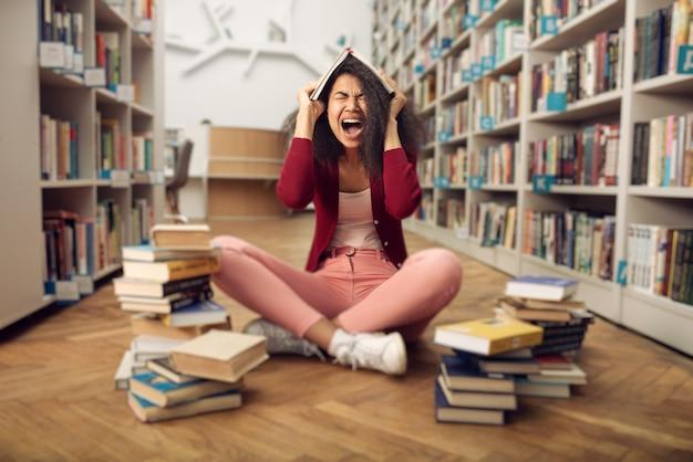 Un étudiant universitaire fatigué a du mal à étudier