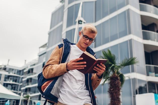 Étudiant universitaire avec livre de lecture de sac à dos marchant près d'un hôtel moderne sur une plage tropicale