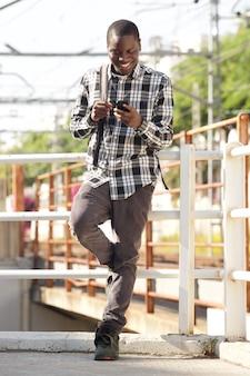 Étudiant universitaire pleine longueur debout avec sac et téléphone portable