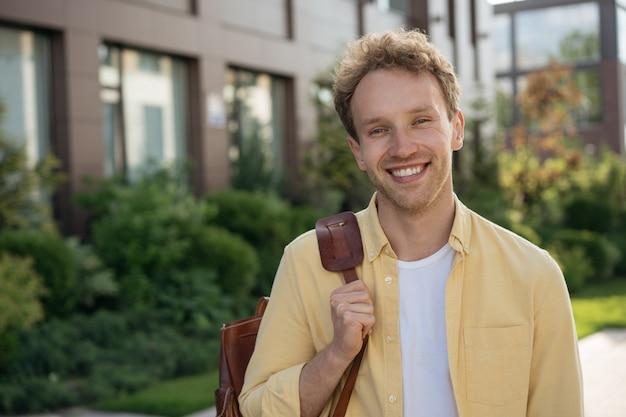 Étudiant universitaire souriant avec sac à dos regardant la caméra debout sur le campus universitaire