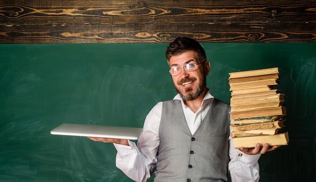Un étudiant universitaire tient des livres et un enseignant masculin d'ordinateur portable avec des livres et un ordinateur portable lisant une copie numérique