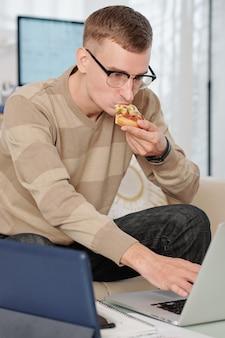 Étudiant à l'université dans des verres mangeant une tranche de pizza en travaillant sur ordinateur portable à la maison