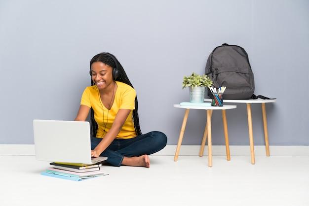 Étudiante adolescente afro-américaine avec de longs cheveux tressés, assise sur le sol