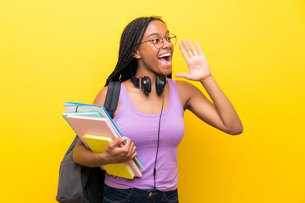 Étudiante adolescente afro-américaine avec de longs cheveux tressés sur un mur jaune isolé criant avec la bouche grande ouverte