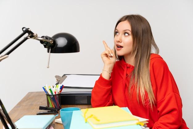 Étudiante adolescente dans sa chambre avec l'intention de réaliser la solution tout en levant un doigt