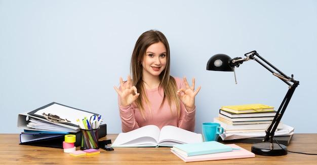 Étudiante adolescente dans sa chambre, montrant un signe ok avec les doigts