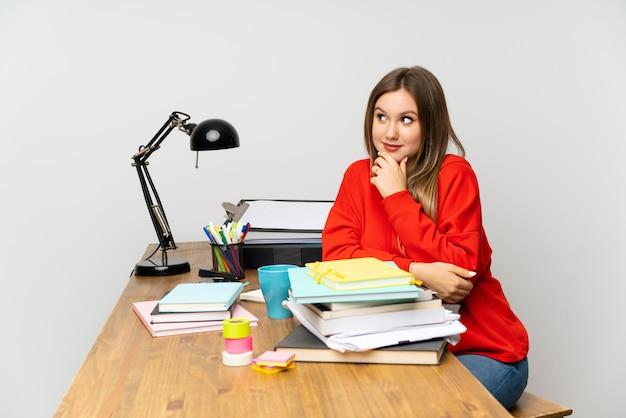 Étudiante adolescente dans sa chambre, pensant à une idée