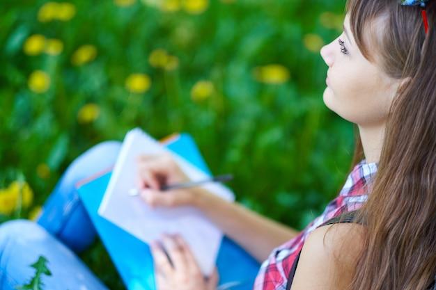 Étudiante adolescente écrit dans le cahier dans le parc. préparation aux examens au collège ou à l'université