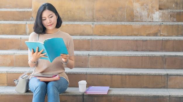 Étudiante adolescente avec le livre de l'éducation et la tasse de café s'asseoir sur l'escalier piéton