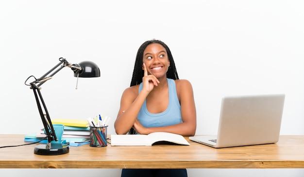 Étudiante adolescente pense à une idée tout en levant les yeux