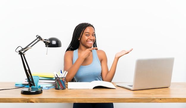 Étudiante adolescente tenant une surface imaginaire sur la paume pour insérer une annonce