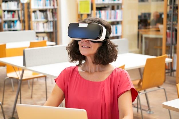 Étudiante adulte utilisant l'expérience de réalité virtuelle pour le travail