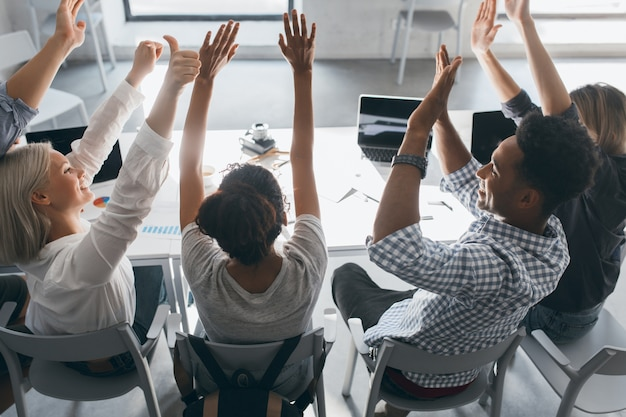 Étudiante africaine bouclée avec sac à dos assis sur une chaise à côté de l'ordinateur et de l'étirement. portrait en intérieur de l'arrière d'employés de bureau paresseux, fatigués de travailler dur avec des ordinateurs portables.