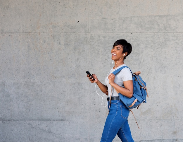 Étudiante africaine marchant avec des écouteurs et un téléphone intelligent
