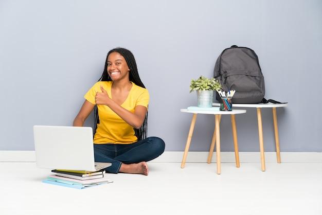 Étudiante afro-américaine étudiante avec de longs cheveux tressés, assise sur le sol, donnant un geste du pouce levé
