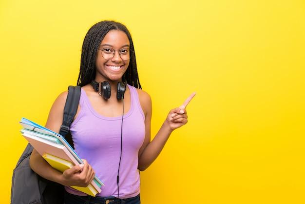 Étudiante afro-américaine étudiante avec de longs cheveux tressés sur un mur jaune, un doigt pointé sur le côté