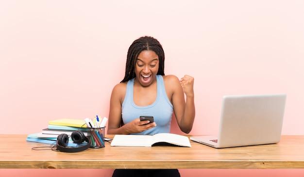 Étudiante afro-américaine étudiante avec de longs cheveux tressés sur son lieu de travail surprise et envoyant un message