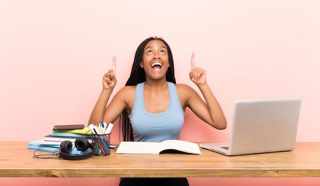 Étudiante afro-américaine étudiante avec de longs cheveux tressés sur son lieu de travail, surprise et pointant vers le haut