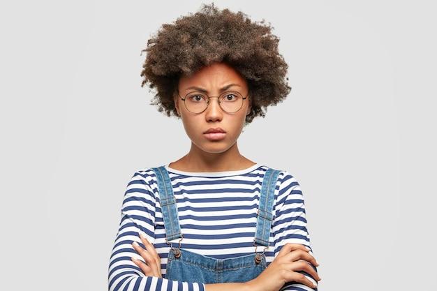 Une étudiante afro-américaine sérieuse en colère garde les bras croisés