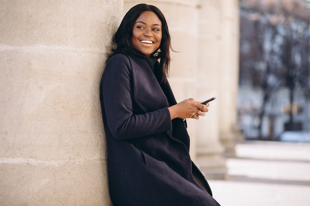 Étudiante afro-américaine avec téléphone de l'université