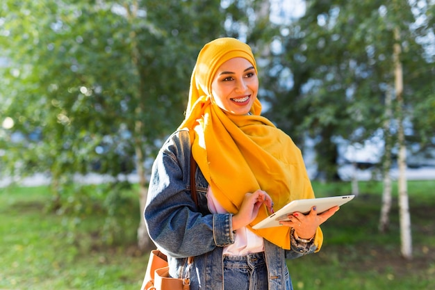 Étudiante arabe. belle étudiante musulmane portant un hijab jaune vif tenant une tablette.