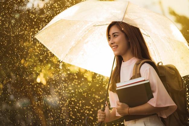 Étudiante asiatique attendant la pluie, elle avait un parapluie.