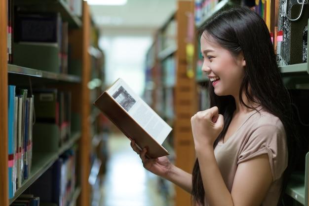 Étudiante asiatique dans la bibliothèque. elle se tient sur une étagère