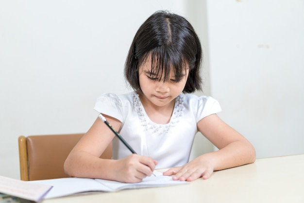 Étudiante asiatique d'enfants de petite fille écrivant sur le cahier faisant des devoirs et l'auto-étude à la maison