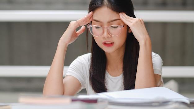 Une étudiante asiatique lit des livres dans une bibliothèque à l'université