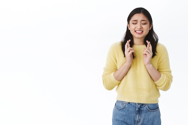 Une étudiante asiatique mignonne et anxieuse s'inquiète d'une mauvaise note au test, croise les doigts bonne chance et ferme les yeux comme suppliant dieu de réaliser le rêve, en attendant le résultat, s'inquiète du résultat, mur blanc