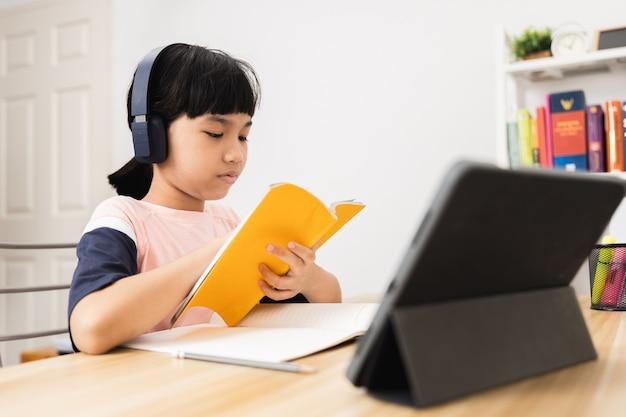 Une étudiante asiatique thaïlandaise apprend en ligne sur une tablette à la maison, un jeune enfant étudie et travaille avec bonheur pendant le verrouillage à cause de covid 19 ou de coronavirus, concept de retour à l'école