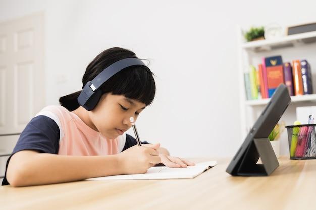 Une étudiante asiatique thaïlandaise apprend en ligne sur une tablette à la maison, un jeune enfant étudie et travaille avec bonheur pendant le verrouillage à cause de covid 19 ou d'un coronavirus