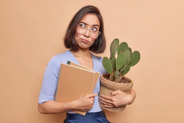 Une étudiante asiatique triste et réfléchie fatiguée de l'étude à distance tient des blocs-notes et un cactus en pot porte de grandes lunettes transparentes regarde au loin pense profondément à quelque chose d'isolé sur un mur beige