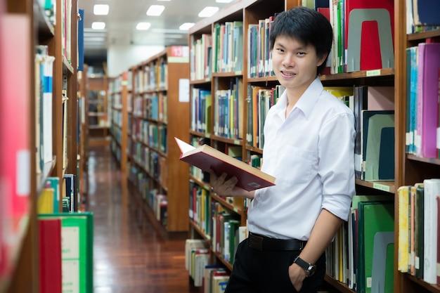 Étudiante asiatique en uniforme en train de lire à la bibliothèque