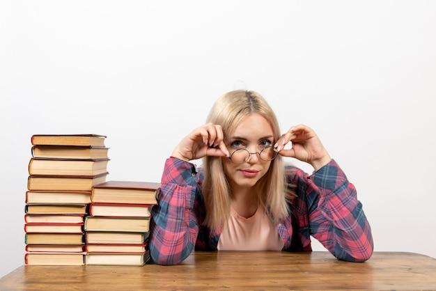 Étudiante assise avec différents livres sur blanc