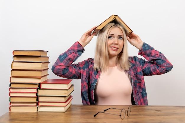 Étudiante assise avec des livres sur blanc