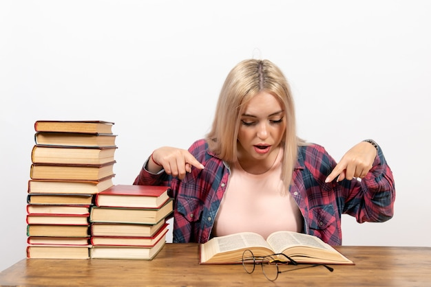 Étudiante assise avec des livres et posant sur le sol blanc lecture école étudiant étude bibliothèque livre