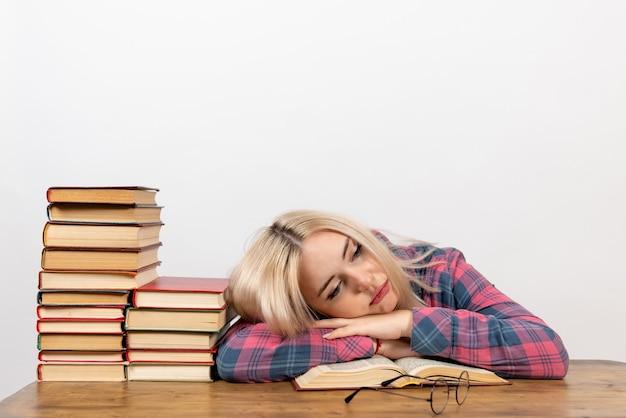 Étudiante assise avec des livres se sentir fatiguée et dormir sur blanc