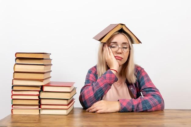 Étudiante assise avec des livres en tenant un sur sa tête sur blanc