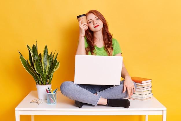 Étudiante assise avec une tasse de café à la main, tient une boisson près du temple, étant fatiguée mais heureuse, regarde avec le sourire, fille portant avec désinvolture, est assise sur une table près d'un pot de fleur, pile de livres.
