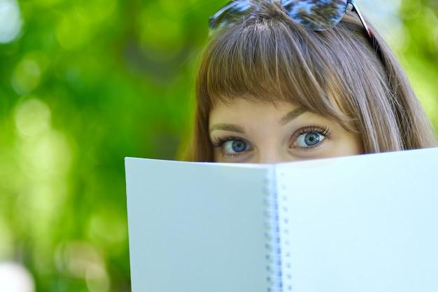 Une étudiante aux yeux bleus se cache derrière un livre. étudiant se cachant derrière le livre