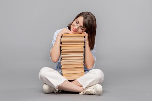 Une étudiante ou une bibliothécaire intelligente avec les jambes croisées gardant la tête au-dessus des livres tout en rêvant de les lire tous