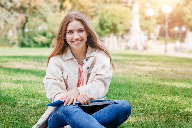 Étudiante blonde assise sur l'herbe, sourit et enseigne des leçons